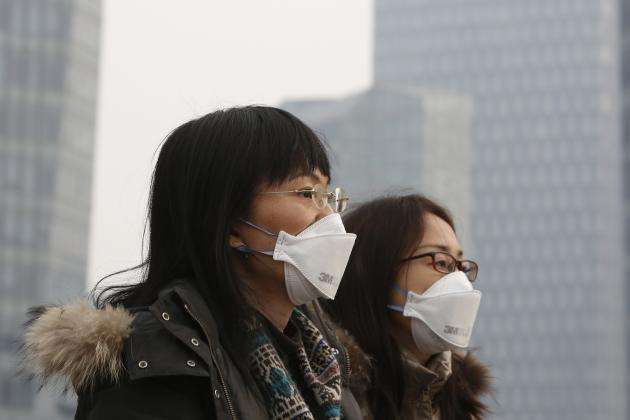 Women wearing face masks walk through the Lujiazui financial district of Pudong on a hazy day in Shanghai
