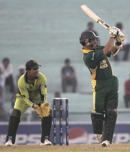 MOHALI, INDIA - OCTOBER 27: Mark Boucher of South Africa is watched by Kamran Akmal as he hits out at the bowling of Muhammad Haffez of Pakistanduring the ICC Champions Trophy match between South Afri