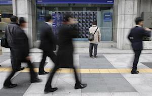 A man looks at a stock quotation board as passers-by walk past, outside a brokerage in Tokyo March 14, 2014. REUTERS/Toru Hanai/Files