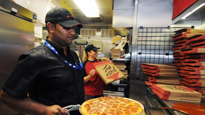 IMAGE DISTRIBUTED FOR PIZZA HUT - Employee Munesh Jairam pulls a pizza from the oven inside the Pizza Hut mobile kitchen in Times Square during The World's Greatest Pizza Party on Sunday, Sept. 8, 2013 in New York City. Pizza Hut celebrated the kickoff of the 2013 football season by serving 5,500 slices, commemorating the brand's 55th anniversary. (Jonathan Fickies/AP Images for Pizza Hut)