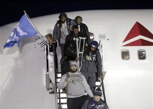 Seahawks' Sherman carries his crutches as he exits the team's chartered flight home after winning NFL Super Bowl XLVIII in Seattle