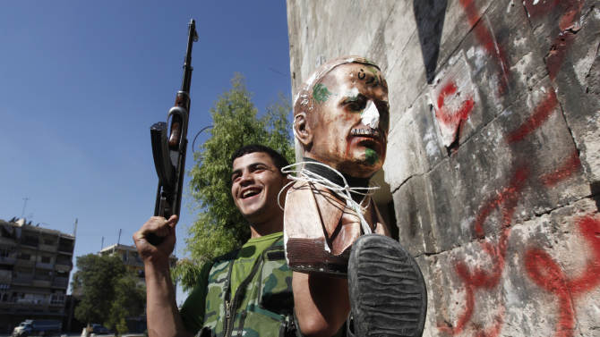 A Free Syrian Army soldier, holds up statue for the late Syrian President Hafez Assad which is attached to a shoe, at the old city of Aleppo city, Syria, Monday Sept. 24, 2012. Syrian warplanes bombed two buildings on Monday in the northern city of Aleppo, killing at least five people including three children from the same family, activists said. (AP Photo/Hussein Malla)
