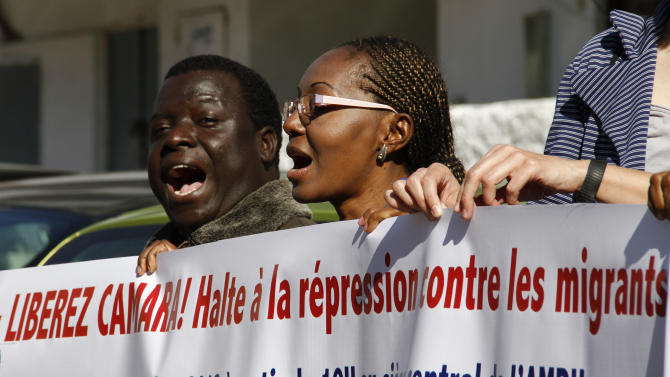Sadio Balde, vice president of the Moroccan Council for Sub-Saharan migrants, left, along with dozens of Moroccan and foreign activists, protests outside a court where Council president Laye Camara is being tried for illegally selling alcohol and cigarettes, Rabat, Morocco, Friday, Nov. 9, 2012. Colleagues of Laye Camara say the charges are trumped-up and are part of a widespread crackdown on legal and illegal black African migrants to this North African kingdom that lies just across the narrow Straits of Gibraltar from Europe. (AP Photo/Paul Schemm)