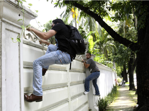 Libyan nationals climb on a gate of the Libyan Embassy at suburban Makati city, eastern Manila in the Philippines, on Thursday Sept. 8, 2011. The two enraged Libyan students barged into their embassy