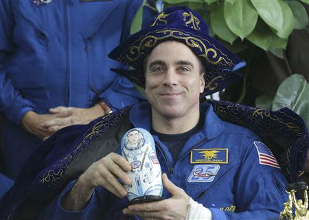 NASA astronaut Cassidy holds up a traditional nesting doll of himself during a press conference at the airport in Karaganda