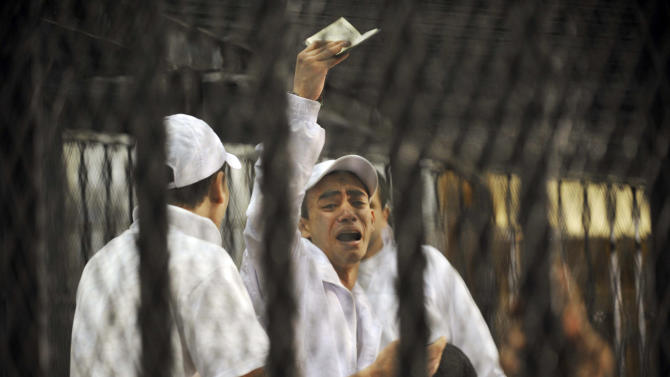 An Egyptian defendant who faces charges relating to deaths after a soccer match in the Mediterranean city of Port Said Feb. 1, 2012, reacts inside a cage during the trial at a court house in Cairo Egypt, Tuesday, April 17, 2012. The opening trial of those charged in connection to the deaths of 75 people killed in Egypt's worst soccer violence was briefly adjourned when defendants erupted in protest to proclaim their innocence. (AP Photo/Hossam Ali)