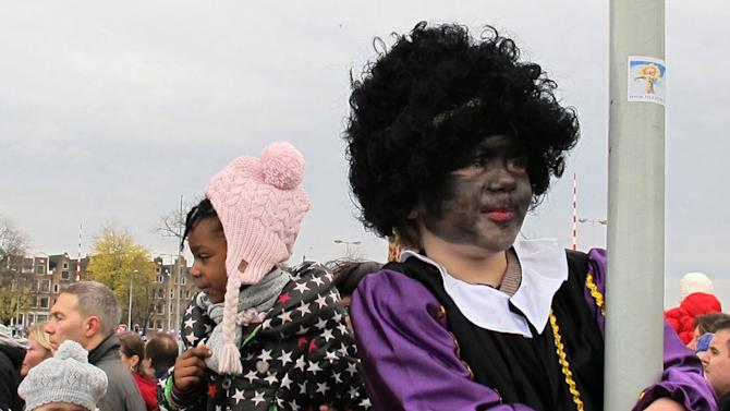 "In this photo taken Sunday, Nov. 18, 2012 a child dressed as ""Zwarte Piet"" or ""Black Pete"", right, is watching a parade after St. Nicholas, or Sinterklaas, arrived by boat in Amsterdam, Netherlands. Foreigners visiting the Netherlands in winter are often surprised to see that the Dutch version of St. Nicholas' little helpers resemble a racist caricature of a black person. The overwhelming majority of Dutch, who pride themselves on tolerance, are fiercely devoted to their holiday tradition and say ""Zwarte Piet"", whose name means ""Black Pete"", is absolutely harmless, a fictional figure who does not represent any race. But now a growing group of Dutch natives are questioning whether this particular part of the tradition should be changed. (AP Photo/ Margriet Faber)"