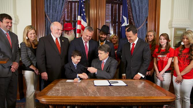 After signing a law protecting Christmas and other holiday celebrations inTexas public schools from legal challenges Texas Governor Rick Perry, center hands the pen to Reagan Bohac, 8, son of the bill's sponsor, Houston Republican Rep. Dwayne Bohac, fifth from left, Thursday, June 13, 2013, in Austin, Texas. (AP Photo/Texas Legislature, Stephen Stephanian)