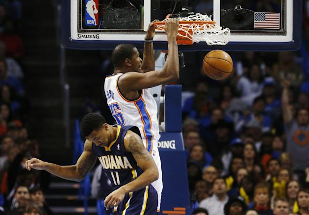 Oklahoma City Thunder forward Kevin Durant (35) dunks behind Indiana Pacers guard Orlando Johnson (11) in the fourth quarter of an NBA basketball game in Oklahoma City, Sunday, Dec. 8, 2013. Oklahoma