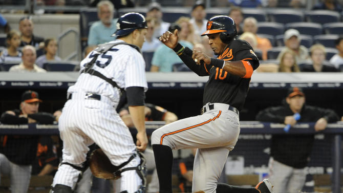 Baltimore Orioles' Adam Jones (10) scores at home plate ahead of the throw to New York Yankees catcher Russell Martin on a single by Chris Davis in the second inning of a baseball game on Friday, Aug., 31, 2012, at Yankee Stadium in New York. (AP Photo/Kathy Kmonicek)