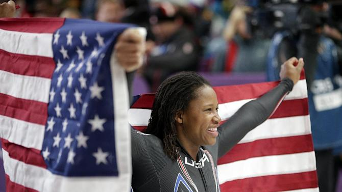 Silver medal winner Lauryn Williams holds the flag after the women's bobsled competition at the 2014 Winter Olympics, Wednesday, Feb. 19, 2014, in Krasnaya Polyana, Russia