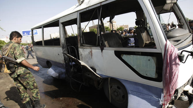 A Yemeni soldier inspects the site of a damaged bus following a bomb attack in Sanaa, Yemen, Sunday, Aug. 25, 2013. A powerful blast ripped through a bus carrying air force personnel down a main street in Yemen's capital on Sunday, causing at least a score of casualties, officials said. (AP Photo/Hani Mohammed)
