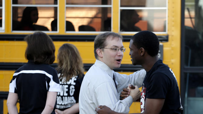 A high school student and teacher from West, Texas greet each other as students arrive for classes at a temporary facility provided by the Connally Independent School District Monday, April 22, 2013, in Waco, Texas. West students returned back  to class today after a massive explosion at the West Fertilizer Co. five days ago damaged three of West's four schools, killed 14 people and injured more than 160 others. (AP Photo/Charlie Riedel)