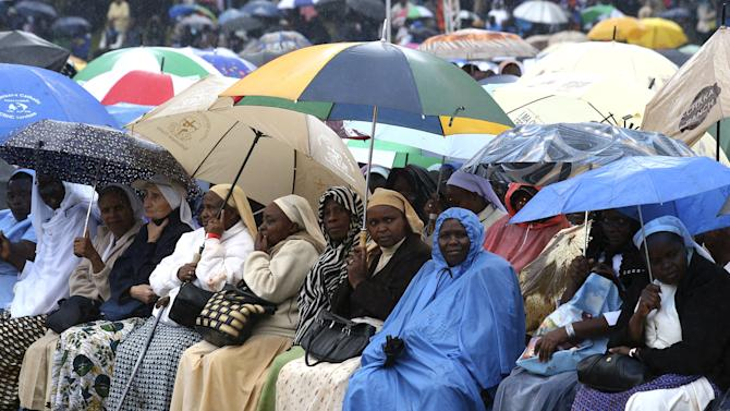 Faithful hold umbrellas as they wait in the rain to attend the mass by Pope Francis in Kenya's capital Nairobi
