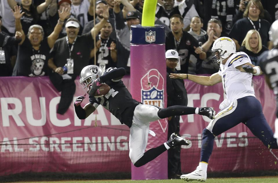 Oakland Raiders cornerback Charles Woodson (24) dives past San Diego Chargers quarterback Philip Rivers to score a touchdown on a fumble recovery during the third quarter of an NFL football game in Oakland, Calif., Sunday, Oct. 6, 2013. (AP Photo/Tony Avelar)