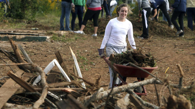 In this photo taken Oct. 19, 2011, Notre Dame fencer Kat Palazzoto pushes a wheelbarrow with debris as she helps cleanup tornado debris in Tuscaloosa, Ala. Twenty-four student athletes from Notre Dame were in Tuscaloosa volunteering time during their fall break to help clean up tornado damaged areas. (AP Photo/The Tuscaloosa News, Robert Sutton)