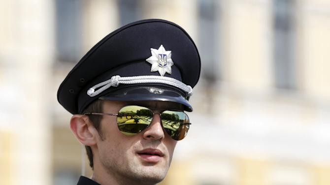 A police officer waits before an oath-taking ceremony, which started up the work of a new police patrol service, in Kiev