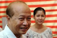 Cambodia's Prince Norodom Ranariddh (L), president of the Norodom Ranariddh Party (NRP), and his wife Ouk Phalla (back R) smile after casting their votes at a polling station in Phnom Penh in June 2012. Ranariddh on Friday announced that he was quitting politics for a second time after he was perceived as an obstacle to a merger between royalist parties