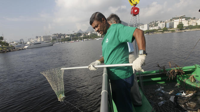 """A worker fishes out trash from a garbage-collecting barge at the Guanabara bay, in Rio de Janeiro, Brazil, Monday, Jan. 6, 2014. The green barge plies the polluted waters of Rio de Janeiro's Guanabara Bay alongside wooden fishing boats but its catch consists not of grouper or swordfish but rather plastic bags, empty soda bottles and a discarded toilet seat. The barge is one of three so-called """"eco-boats,"""" floating garbage vessels that are a key part of authorities' pledge to clean up Rio's devastated Guanabara Bay before the city – and the waterway itself – plays host to the 2016 Olympic games. (AP Photo/Silvia Izquierdo)"""