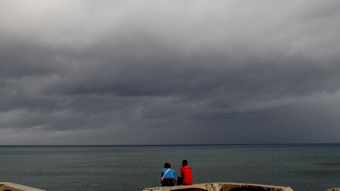 A couple sit on a bench under cloudy skies along the shore of Santo Domingo, Dominican Republic, Thursday, Aug. 23, 2012. Tropical Storm Isaac churned toward the Dominican Republic and Haiti on Thursday, threatening to strengthen into a hurricane. (AP Photo/Manuel Diaz)