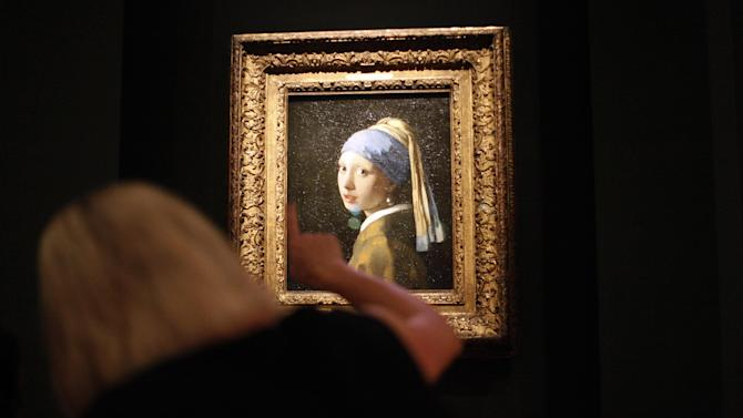 "This June 19, 2013 photo shows Johannes Vermeer's famous painting ""Girl With a Pearl Earring"" part of the ""Girl with a Pearl Earring: Dutch Paintings from the Mauritshuis"" exhibit during a media preview at the High Museum of Art in Atlanta. The exhibit, which opens Sunday and runs through Sept. 29, includes 34 other works from the Dutch Golden Age. (AP Photo/Jaime Henry-White)"