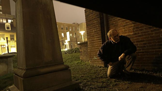 In this Jan. 15, 2013 photo, Jeff Jerome looks through a passage underneath Westminster Hall in Baltimore, where the mysterious Poe Toaster would sometimes slip through on his way to place three roses and an unfinished bottle of cognac upon Edgar Allan Poe's original grave. His identity is a great modern mystery, and just as mysteriously, the tradition ended four years ago. (AP Photo/Patrick Semansky)