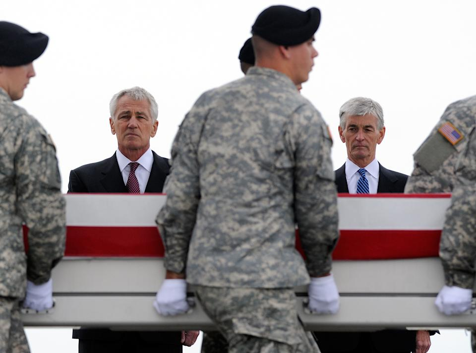 Defense Secretary Chuck Hagel, left, and Army Secretary John McHugh, right, watch an Army carry team move a transfer case containing the remains of Pfc. Cody J. Patterson Wednesday, Oct. 9, 2013 at Dover Air Force Base, Del. According to the Department of Defense, Patterson, 24, of Philomath, Ore., died Oct. 6, 2013 in Zhari district, Afghanistan of injuries sustained when enemy forces attacked his unit with an improvised explosive device. (AP Photo/Steve Ruark)