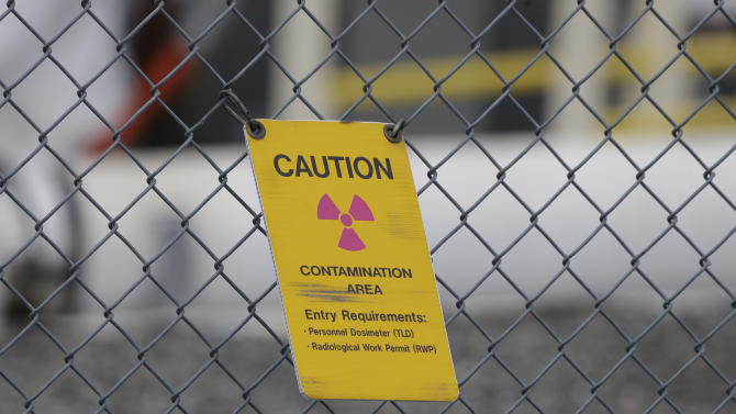 A sign warning of radioactive contamination dangles from a fence at the 'C' Tank Farm at the Hanford Nuclear Reservation, Wednesday, March 6, 2013, near Richland, Wash. Gov. Jay Inslee toured Hanford Wednesday and met with Dept. of Energy officials in order to learn more about tanks on the site that are leaking radioactive waste. (AP Photo/Ted S. Warren)