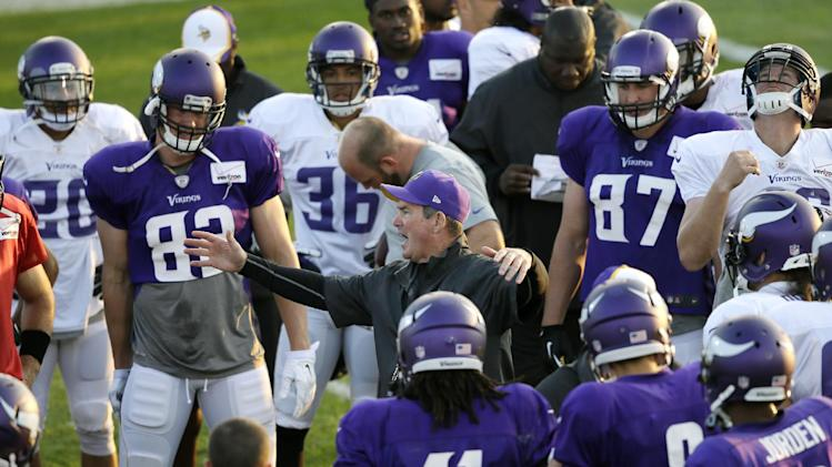 Minnesota Vikings head coach Mike Zimmer, center, talks to his team during an NFL football training camp practice, Monday, July 28, 2014, in Mankato, Minn