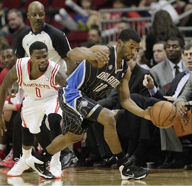 Orlando Magic point guard Ronnie Price (10) steals the ball from Houston Rockets point guard Aaron Brooks (0)during the first quarter of an NBA basketball game Sunday, Dec. 8, 2013, in Houston