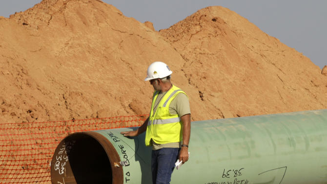 A pipeline worker walks the length of a pipe as work continues Thursday, Oct. 4, 2012, in Sumner,  Texas. Oil has long lived in harmony with farmland and cattle across the Texas landscape, a symbiosis nurtured by generations and built on an unspoken honor code that allowed agriculture to thrive while oil was extracted. (AP Photo/Tony Gutierrez)