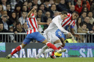 Real Madrid's Cristiano Ronaldo from Portugal duels for the ball with Atletico de Madrid' Eduardo Salvio of Argentina, left, and Luis Amaranto Perea of Colombia, right, during their Spanish La Liga soccer match at the Santiago Bernabeu stadium, in Madrid, Spain, Saturday, Nov. 26, 2011. (AP Photo/Daniel Ochoa de Olza)
