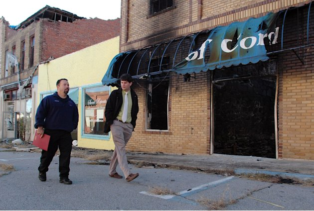 In this Tuesday, Nov. 13, 2012 photo, Cordova, Ala., Fire Chief Dean Harbison, left, and Mayor Drew Gilbert walk through the town's tornado-damaged downtown. The area looks much as it did right after