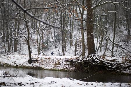 A pedestrian walks through snow in the Valley Forge National Park in Pennsylvania