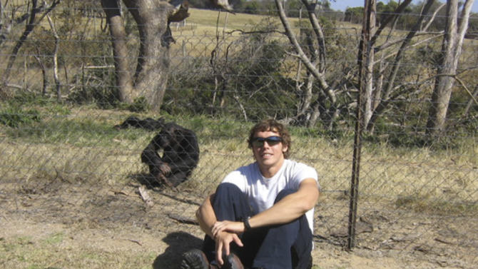 This undated photo provided by the Facebook group HelpAndrewOberle shows graduate student Andrew Oberle sitting with a chimp. Doctors are reporting improvement in the condition of Oberle, who was attacked by chimps he was studying in South Africa. (AP Photo/HelpAndrewOberle)