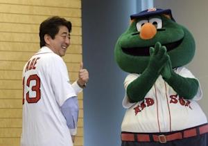 Japan's PM Abe smiles as he wears a jersey of Boston Red Sox, while Red Sox mascot Wally looks on at Abe's office in Tokyo