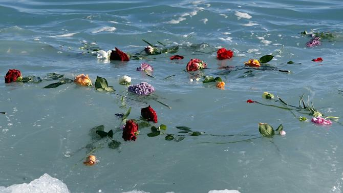 Flowers float into the Mediterranean sea on April 28, 2015 in Nice, France, in honor of migrants who drowned trying to reach Europe