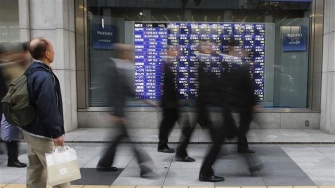 A man looks at a stock quotation board as passers-by walk past, outside a brokerage in Tokyo