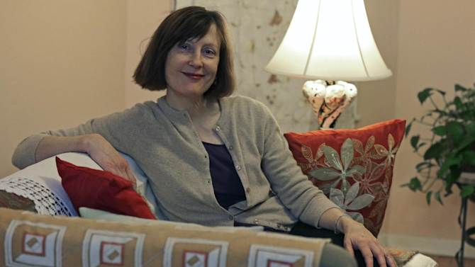 Valerie Spain poses in the living room of her Cambridge, Mass., home, Thursday, Jan. 17, 2013.  The 57-year-old former operations manager was able to find insurance through the subsidized Commonwealth Care program created under the a Massachusetts healthcare law. She pays no premiums, but is charged a $20 co-pay for visits to her doctor's office.(AP Photo/Charles Krupa)