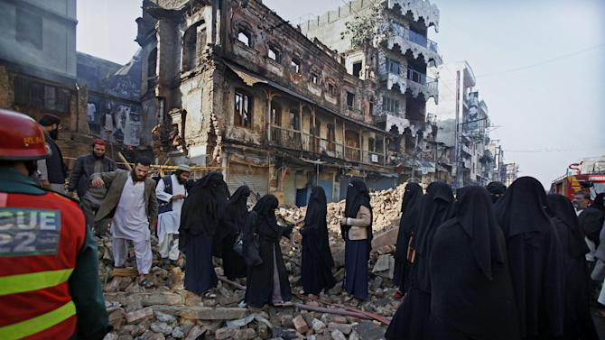 Female students of an Islamic seminary look a burnt building, which was torched in the Friday's sectarian clashes, in Rawalpindi, Pakistan, Monday, Nov. 18, 2013. Pakistani police say the government has lifted a curfew in the garrison city of Rawalpindi that was imposed after eight Sunni Muslims were killed in a sectarian clash with Shiites marching in a religious procession. (AP Photo/Anjum Naveed)