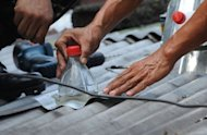 Soldiers install solar light bottles on a roof in a Manila shanty town. The idea is simple - fill discarded soft drink bottles with water, place them in roofs and allow the refracted light to brighten homes during the day