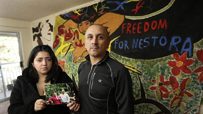 Grisel Rodriguez, left, and Jose Avila, right, pose for a photo, Tuesday, Nov. 26, 2013, in their apartment in Renton, Wash. They are holding a photo of Avila with his wife, Nestora Salgado, who has been detained since she was arrested Aug. 21, 2013 in the state of Guerrero, south of Mexico City, where she had been leading a vigilante group targeting police corruption and drug cartel violence. Rodriguez is Salgado's daughter. (AP Photo/Ted S. Warren)