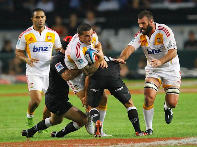 New Zealand Waikato Chiefs' Sonny Bill Williams (C) is tackled as teammates Alex Bradley (R) and Lelia Masaga (L) look at him during the Super 15 rugby union match Sharks of Durban vs Waikato Chiefs o