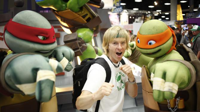 COMMERCIAL IMAGE - A fan poses for a photo with teenage mutant ninja turtles at the Nickelodeon booth at Comic-Con on Thursday, July 12, 2012, in San Diego, Calif. (Photo by Joe Kohen/Invision for Nickelodeon/AP Images)