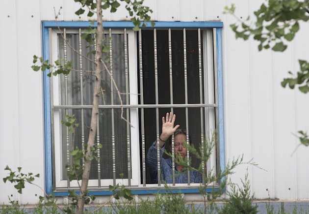 American Chip Starnes, co-owner of Specialty Medical Supplies, waves from a window after he was held hostage by workers inside his plant at the Jinyurui Science and Technology Park in Qiao Zi township of Huairou District, on the outskirts of Beijing, China Monday, June 24, 2013. An American executive said Monday Starnes has been held hostage for four days at his medical supply plant in Beijing by dozens of workers demanding severance packages like those given to co-workers in a phased-out department. (AP Photo/Andy Wong)