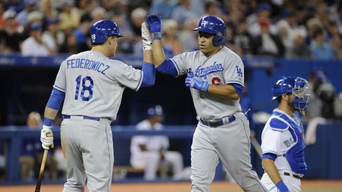 Los Angeles Dodgers' Jerry Hairston Jr., center, high fives teammate Tim Federowicz (18) after scoring a solo home run during the sixth inning of a baseball game against the Toronto Blue Jays Tuesday July 23, 2013 in Toronto. (AP Photo/The Canadian Press, Jon Blacker)