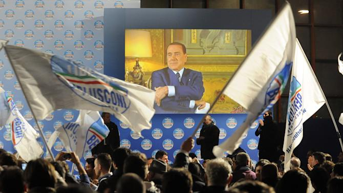 Supporters wave flags in front of a giant monitor broadcasting a message by Silvio Berlusconi during a center-right coalition rally in Naples, Italy, Friday, Feb. 22, 2013. Silvio Berlusconi has skipped his last campaign rally before Italian elections because of an eye problem. The 76-year-old media mogul is trying to make a comeback, to win a fourth term as premier. He was supposed to address a rally in Naples on Friday, but instead spoke to supporters in a video message. Italian media quoted his personal doctor, Alberto Zangrillo, as saying Berlusconi was advised to skip the rally, because he has a posterior vitreous detachment in an eye. In the condition, common in the elderly, a gel-like substance naturally in the eye pulls away from the retina. (AP Photo/Salvatore Laporta)