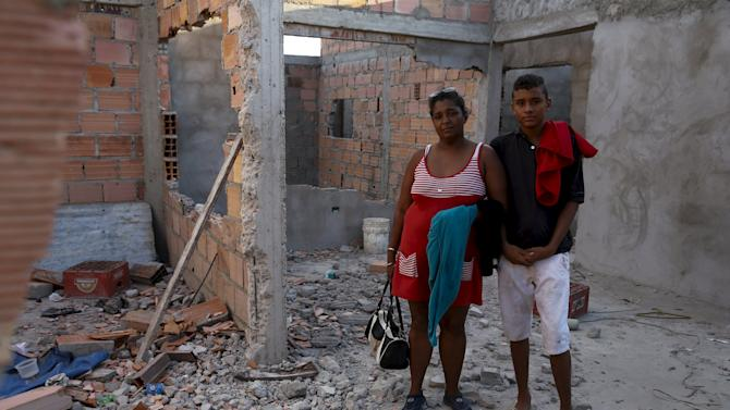 Colombian Mayerlis Acosta, 43, who has been living in Venezuela for 15 years, and her son Wilinton, 14, pose for a picture at their partially dismantled house, before crossing to Colombia through the Tachira river at San Antonio in Tachira state
