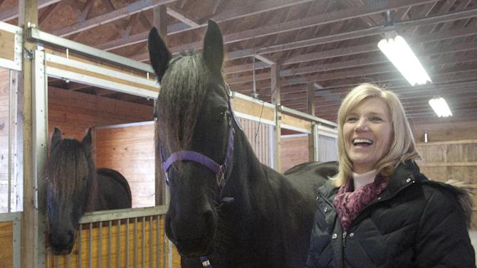 "Sandy Bonem, right, holds  her horse Mariska, in her stable at  Larkin Township, Mich. in Midland County on Feb. 13, 2013.  Mariska, a 9-year-old Friesian, learned to open latches at Misty Meadow Farms and she's been nicknamed ""Houdini Horse"" by the Midland-area's farm owners Sandy and Don Bonem. A YouTube video Sandy Bonem posted has more than 700,000 views. (AP Photo/The Saginaw News, Jeff Schrier) ALL LOCAL TV OUT; LOCAL TV INTERNET OUT"