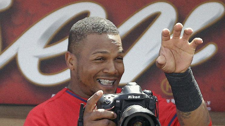 Los Angeles Angels's Erick Aybar has fun with a camera before an exhibition spring training baseball game against the Chicago White Sox, Thursday, March 13, 2014, in Tempe, Ariz